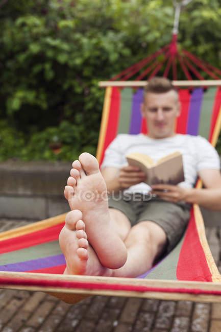 Мужчина читает книгу о гамаке днем — стоковое фото