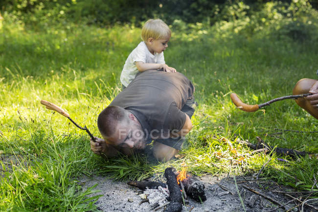 Man with son (2-3) igniting camp fire — Stock Photo