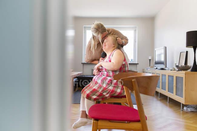 Mutter küsst Tochter beim Haareputzen — Stockfoto