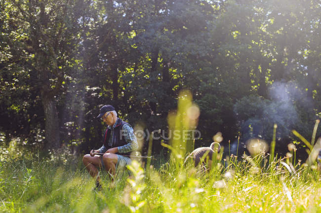 Man sharpening stick in meadow — Stock Photo