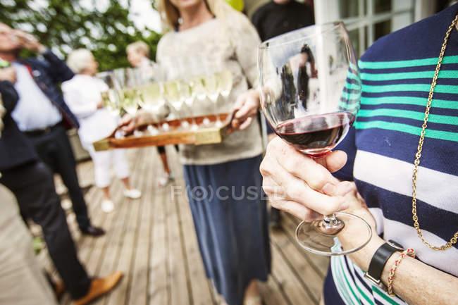 Donna che tiene un bicchiere di vino rosso alla festa in giardino — Foto stock