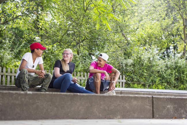 Adolescente e ragazzi adolescenti (14-15) che si siede sul marciapiede — Foto stock