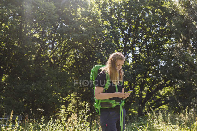 Young woman using phone in meadow — Stock Photo