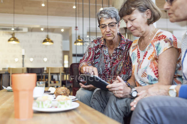 Tre donne che utilizzano tablet digitale in caffè — Foto stock