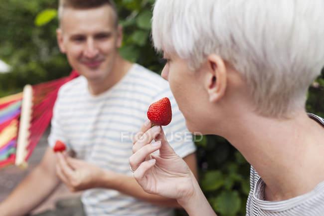 Пара їсти полуницю в саду — стокове фото