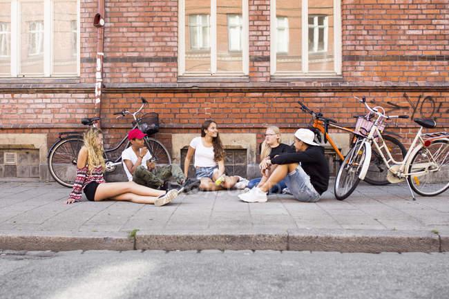 Teenage girls and teenage boys (14-15) sitting on sidewalk — Stock Photo