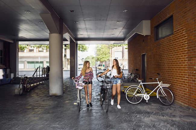 Due ragazze adolescenti (14-15), passeggiate con le biciclette — Foto stock