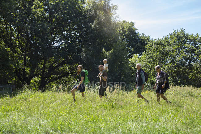 Family walking in meadow during daytime — Stock Photo