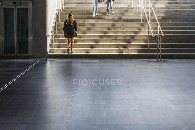 Woman walking up stairs from below — Stock Photo