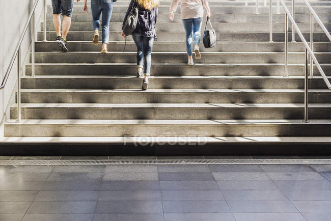 Four people walking up stairs — Stock Photo