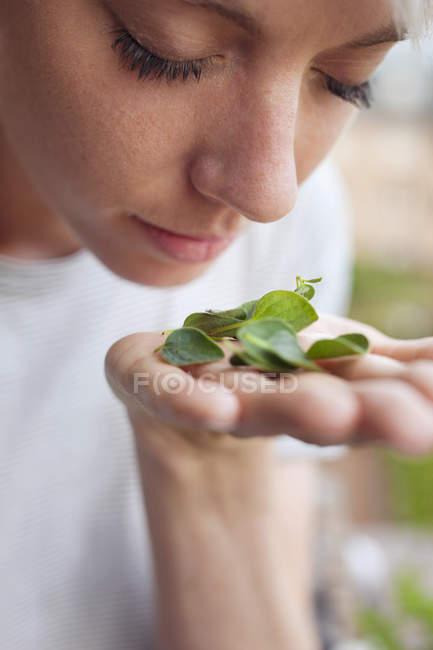 Mujer oliendo hierbas frescas, primer plano - foto de stock
