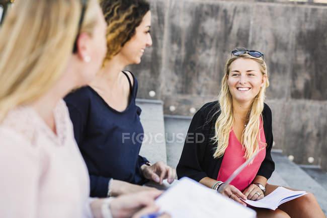 Три молодые женщины, сидя на шагах — стоковое фото