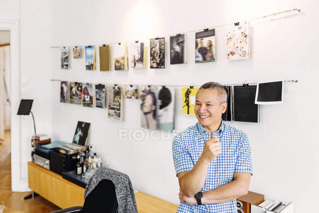 Smiling editor against wall with magazine covers — Stock Photo