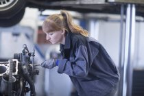 Woman mechanic repairing engine — Stock Photo