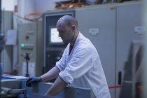 Homme en laboratoire manteau dur travail — Photo de stock