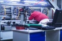 Worker in uniform adjusting equipment — Stock Photo