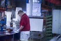 Homme travaillant dans une usine industrielle — Photo de stock