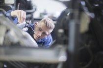 Blond man repairing printing equipment — Stock Photo