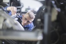 Blond man repairing printing equipment — Stock Photo