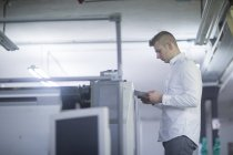 Працівник з документи в руках оглядають принтера — стокове фото