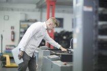 Arbeiter mit Papieren in Händen Inspektion Drucker — Stockfoto