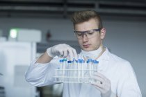 Scientist looking at test tubes — Stock Photo