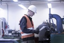 Engineer working at machine at industrial plant — Stock Photo