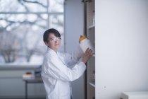 Жіночий вченого беручи контейнер з полиці — стокове фото