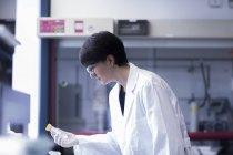Female scientist holding test tube — Stock Photo