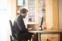 Людина, сидячи на стіл і працюють на комп'ютері — стокове фото