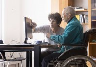 Woman in wheelchair working on computer with partner — Stock Photo