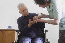Woman giving pills to woman in wheelchair — Stock Photo