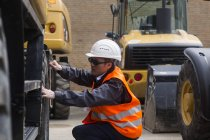 Industrial worker inspecting digger — Stock Photo