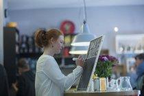 Рыжая девушка бармен на работе — стоковое фото