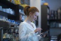 Girl bartender using phone — Stock Photo