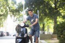 Jeune homme debout près de scooter — Photo de stock