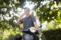 Man talking on phone standing near scooter — Stock Photo