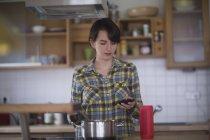 Donna che cucina nella cucina con smartphone — Foto stock