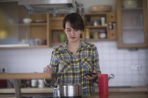Woman cooking in kitchen with smartphone — Stock Photo