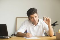 Male manager writing notes while looking at detail — Stock Photo