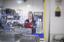 Female engineer inspecting equipment at industrial plant — Stock Photo