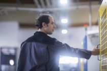 Hombre Ingeniero examinar maquinaria en planta industrial - foto de stock