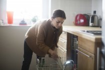Woman putting crockery in dishwasher — Stock Photo