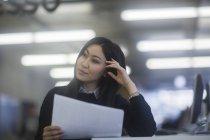 Frau hält Dokumente und denken im Büro — Stockfoto
