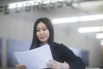 Woman looking down at documents in hands — Stock Photo
