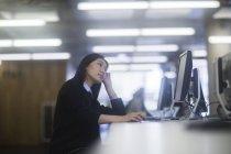 Жінка сидить на столі в офісі і спершись на руки — стокове фото