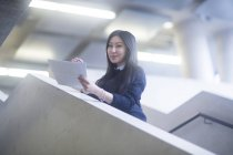 Woman standing on stairs with papers and looking in camera — Stock Photo