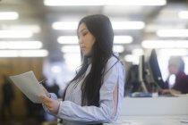 Frau schreiben mit Stift auf Papier im Büro — Stockfoto