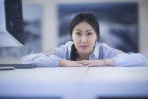 Femme s'appuyant sur le bureau et vous cherchez à huis clos — Photo de stock