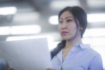 Mujer pensativa sosteniendo papeles y mirando lejos - foto de stock